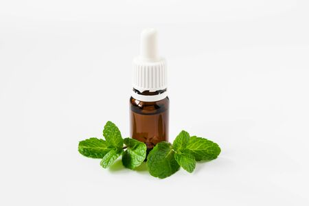 isolated glass bottle with aromatic oil and a sprig of mint on a white background
