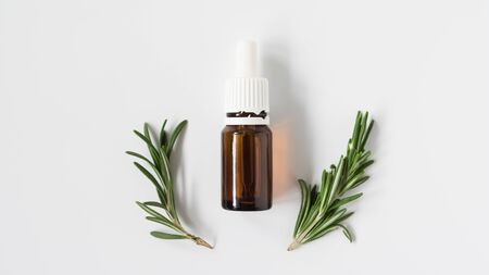 glass bottle with aromatic oil and a sprig of rosemary on a white background