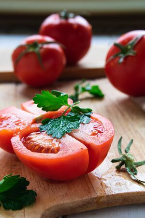 ripe tomatoes on a wooden board with parsley closeup on the table