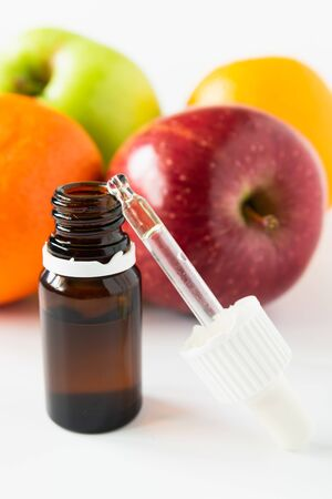 cosmetic concept, glass bottle with serum with alpha hydroxy acids on a background of fruit Stock Photo