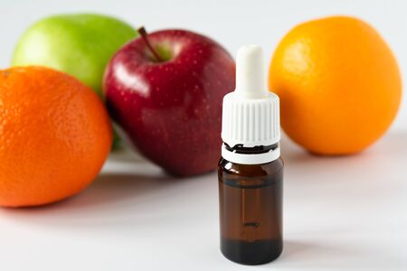 glass bottle with serum with alpha hydroxy acids on a background of fruit