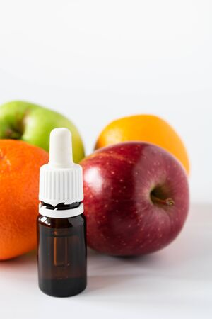 cosmetic concept, glass bottle with serum with alpha hydroxy acids on a background of fruit