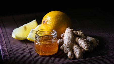ginger, lemon and a jar of honey on a dark background