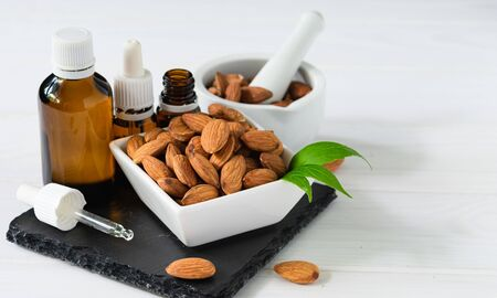 almonds in a white plate and glass bottles with oil on a black tray on a wooden table