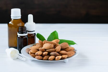 almonds in a white plate and glass bottles with oil on a wooden table