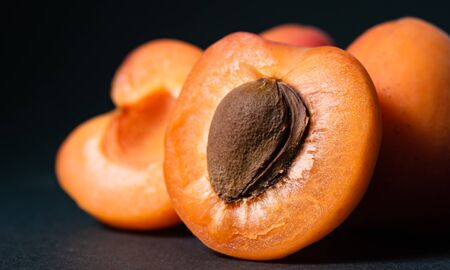 slice of ripe apricot with a seed on a dark background, close-up
