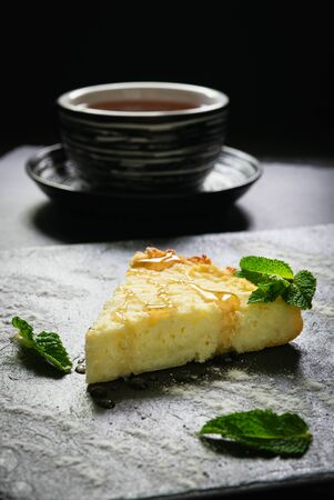 cheesecake sprinkled with icing sugar and with sweet syrup with mint on a black pond, a cup with a drink Archivio Fotografico