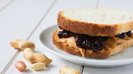 fast food, snack, peanut butter and fruit jam sandwich on a white wooden table