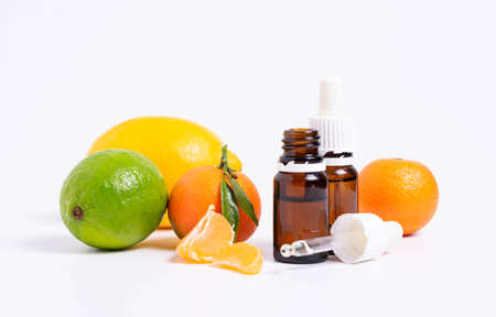 Lime essential oil in glass bottle and fresh green lime fruit isolated on white background.