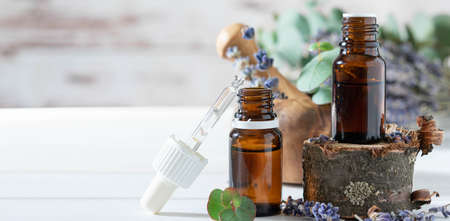 organic cosmetics concept, glass bottle with oil, pipette and lavander flowers, eucaliptus on light wooden background Banque d'images
