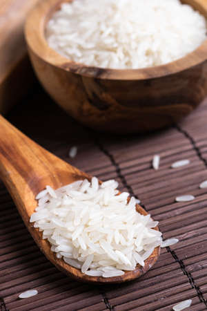 rice grains on a wooden spoon on the table close-up Reklamní fotografie