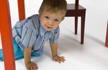 Un ni�o se esconde debajo de la mesa. Foto de archivo - 2489202