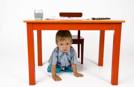hides: A child hides under the table.