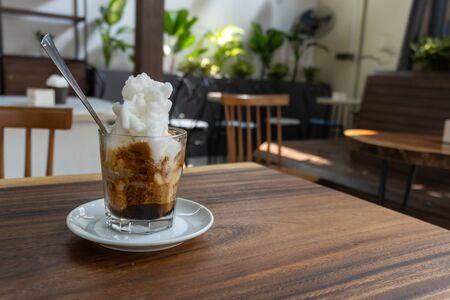 Ice coffee with ice cream on a wooden table