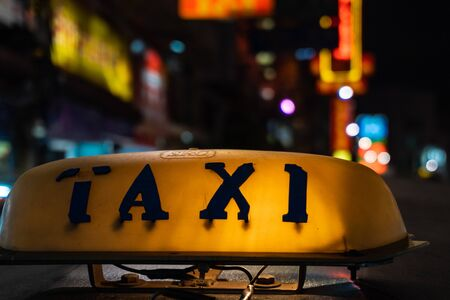 Night picture of a tuk tuk's taxi sign. Old taxi sign on the roof glowing in the dark
