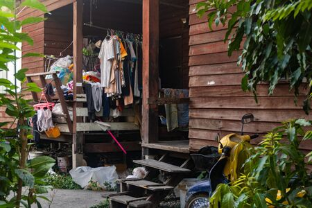 A small courtyard of a local house in Thailand, the clothes hung up to dry and an old motorcycle.