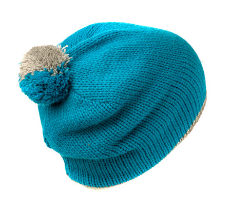beanie: blue knitted beanie with pompom  isolated on white background .