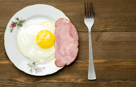 side plate: fried eggs sunny side up on a plate on a wooden background. Stock Photo
