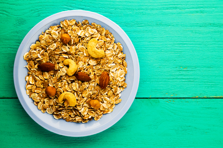 oatmeal: Oatmeal with nuts (hazelnuts, cashews, almonds). Oatmeal on a wooden table. Oatmeal top view. Healthy food .