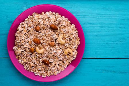 muesli with nuts(hazelnuts, cashews, almonds). muesli on a wooden table. muesli top view . healthy food .