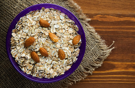 oatmeal:   Oatmeal with nuts   almonds . Oatmeal  on a wooden background. Healthy food . Stock Photo
