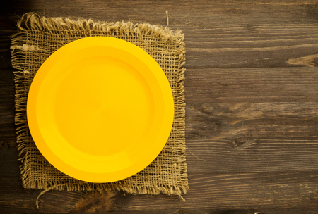 plate on a wooden background.yellow plate . plate top view. copy space . Stock Photo