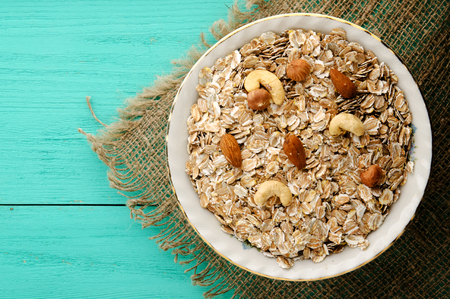 Oatmeal with nuts (hazelnuts, cashews, almonds). Oatmeal on a wooden table. Oatmeal top view. Healthy food Stock Photo