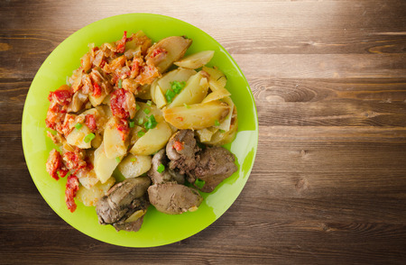 fried liver with potatoes and stewed tomatoes. fried liver on plate on a wooden background Stock Photo