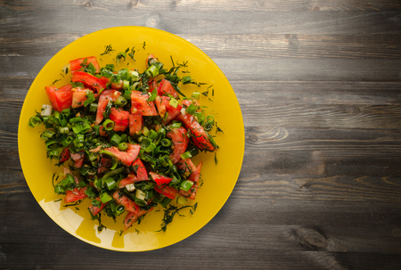 vegetarian food . tomatoes, onion, fennel on a plate on a wooden background. healthy food Stock fotó