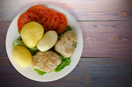 cutlet with potatoes on a plate. cutlet with potatoes on a wooden background