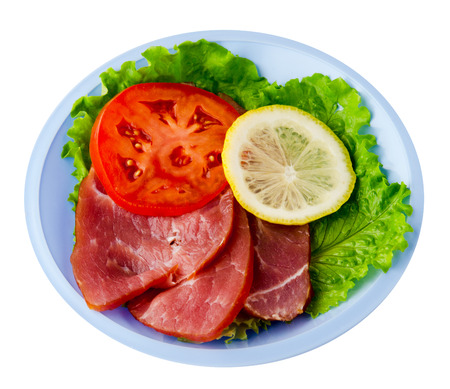 ham with salad, tomato and lemon on a plate. ham on a plate isolated on a white background Stock Photo