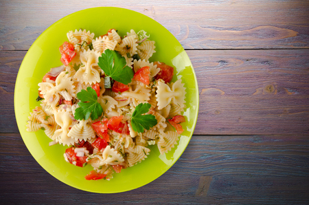 pasta on a plate. pasta tomatoes, onions, cabbage on a wooden background