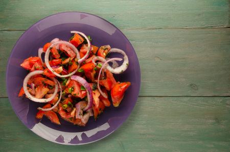 vegetarian food . tomatoes, onion, fennel on a plate on a wooden background. healthy food Imagens