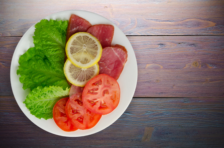 ham with salad, tomato and lemon on a plate. ham on a wooden background .ham top view Stock Photo