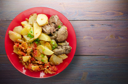 fried liver with potatoes and stewed tomatoes. fried liver on plate on a wooden background