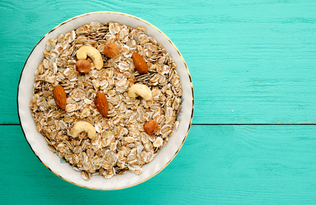 Oatmeal with nuts. Oatmeal on a wooden table. Oatmeal top view. Healthy food