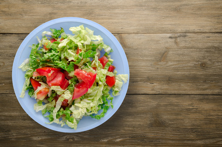 vegetarian food . salad of cabbage tomato on a plate on a wooden background. healthy food Stock Photo