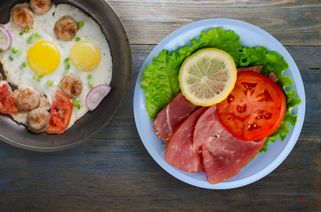 ham with salad, tomato and lemon on a plate. ham on a wooden background .ham top view Stock Photo - 92512831