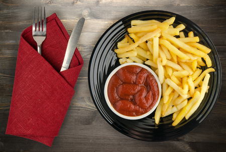 french fries with ketchup on a wooden background. french fries on a plate Stock Photo