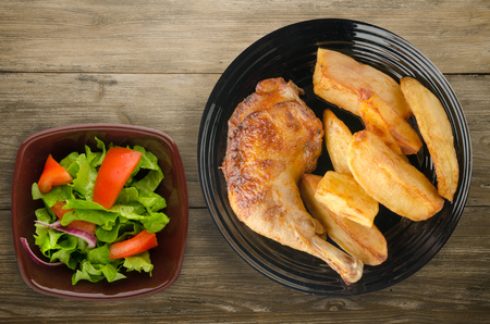 Chicken thigh with French fries on a wooden background. chicken thigh on a plate. rustic food Banque d'images