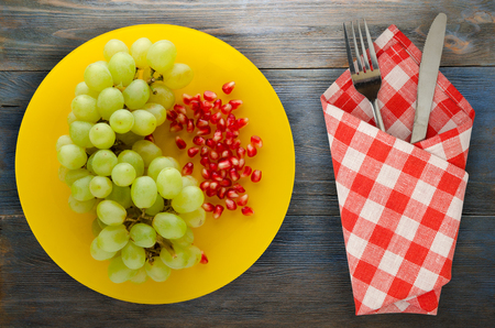 grapes, pomegranate isolated on white background. grapes, pomegranate on a plate Standard-Bild