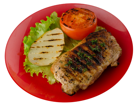 pork grilled with potatoes and tomato isolated on white background. grilled pork on a plate top view