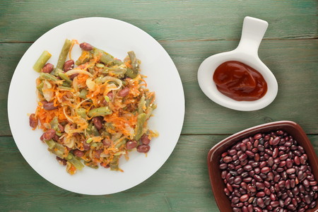 Salad of beans, asparagus, onion, carrot and sesame on a plate on a wooden background. Banque d'images