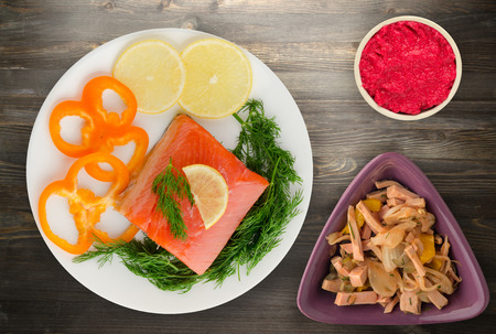 red fish trout fillets on a plate. fish trout on a wooden background. trout with dill, lemon and pepper