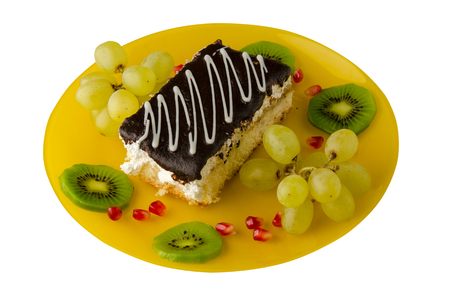 dessert of cake and fruit (grapes, kiwi, pomegranate)  isolated on white background. dessert on a plate top view .