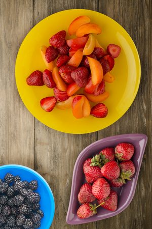 healthy food. Strawberries and apricots on a plate. Fruits on a wooden background.