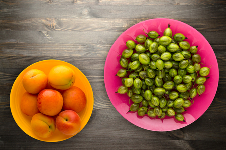 gooseberries on plate  on wooden background. green gooseberry top view. healthy food .