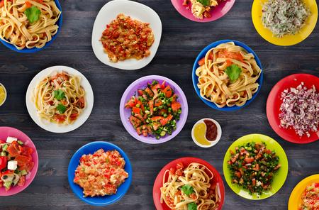 테이블에 야채와 소스와 함께 파스타입니다. 접시에 스파게티입니다. 지중해 음식