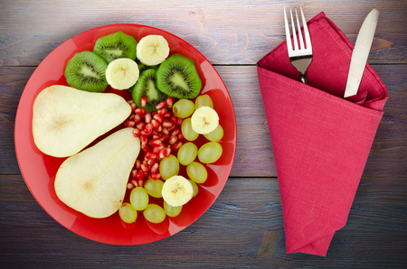 fruit mix (pear, kiwi, grapes, banana, pomegranate) on a wooden background. fruit on a plate Banque d'images