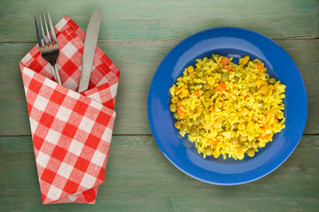 Asian healthy food. Rice (yellow) on a plate with vegetables. Eastern food on a wooden background.